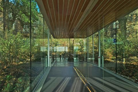 The sloping corridor between the public and private rooms is lined with mirror-polished steel, reflecting the woodland outside.
